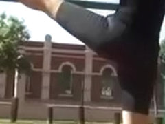 Flexible woman in spandex stretches in the park