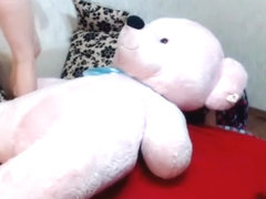 Slender naked hotty plays with large teddy bear