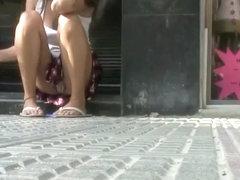 Peeping under sitting girl's skirt