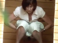 Pissing older woman zoomed by a voyeur