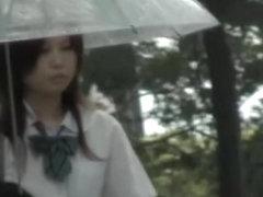 Asian schoolgirl gets street sharking on a rainy day.
