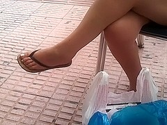 Candid dangling in flip flops