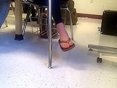 Girl dangling flip flops in class