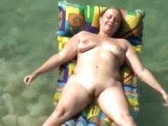 Chubby nudist woman with tattooed arm