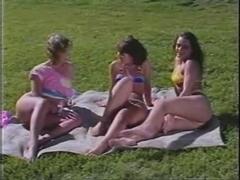 Retro lesbian threesome in a public garden in the sun