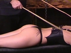 Brunette Hair in leather bustier lies on bench for stud who takes 2 canes to her as