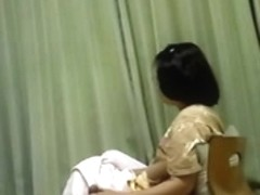 Mature Asian wife gives her husband a handjob while watching TV