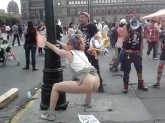 Female agitator pees and poops on a poster at a rally in protest to the government