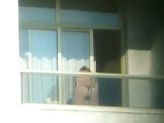 Topless brunette hottie filmed from a window
