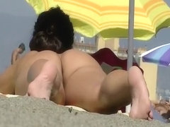 Nudist sunbathing and reading a book