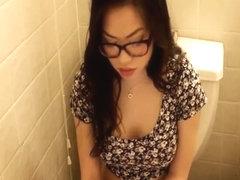 Girl in glasses pissing in toilet
