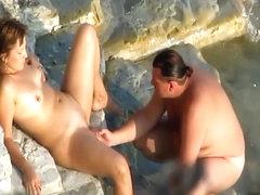 Romantic masturbation on a rocky beach