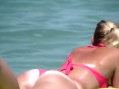 Pale buttocks in a pink thong bikini