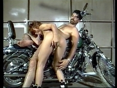 Leggy redhead bows over motorcycle and acquires anal screwed by wild hog in garage
