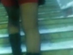 Chick flashing her black stockings with the red tops outdoor