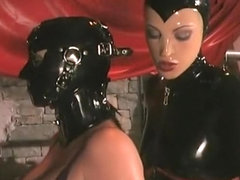 Gorgeous mistress clad in a latex suit teases her buxom slave