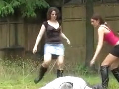 Two young mistress boots trampling outdoor