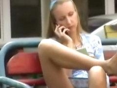 Girl seating in a bench shaved pussy upskirt